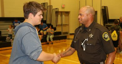 """Sean Barnett, ninth grade, Zemmer Middle School, shakes the hand of Lapeer County Sheriff's Dept. Deputy Jimmy White during Thursday's open house at the school. Barnett says it """"feels good"""" to know Deputy White is there. Photo by Andrew Dietderich"""